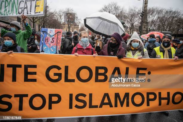 Protestors hold a banner at a demonstration against the draft global security bill and growing Islamophobia on December 12, 2020 in Paris, France....