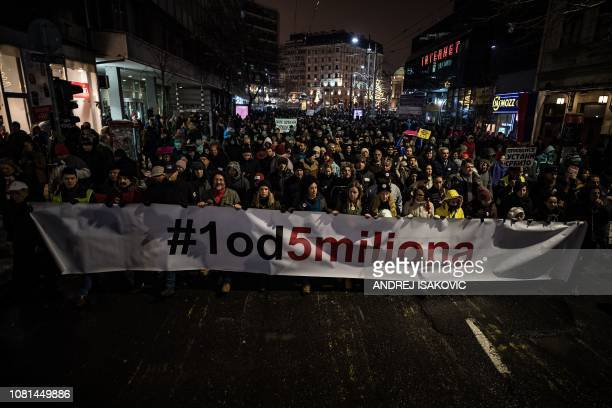 Protestors hold a banner reading 1 out of 5 millions during a demonstration against the Serbian president in the capital Belgrade on January 12 2019...