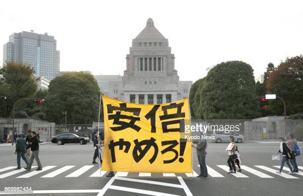 Protestors hold a banner reading Quit Abe in front of the parliament building in Tokyo on Nov 3 2017 Demonstrators gathered to express their...