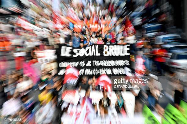 TOPSHOT Protestors hold a banner reading Social is burning during a oneday nationwide strike over President Emmanuel Macron's policies on October 9...