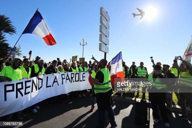 TOPSHOT Protestors hold a banner reading 'The People speaks out' on the 'Promenade des Anglais' during a protest of Yellow vests against rising oil...