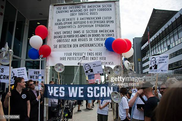 Protestors hold a banner reading Yes We Scan and posters reading Stasi 20 depicting US President Barack Obama wearing headphones in allusion of a...