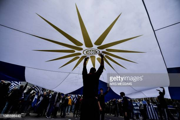 TOPSHOT Protestors hold a flag of the Greece's Macedonia region in front of the Greek Parliament in Athens on January 20 2019 during a demonstration...