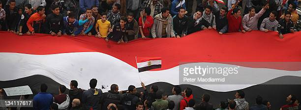 Protestors hold a giant Egyptian flag aloft in Tahrir Square on November 26 2011 in Cairo Egypt Thousands of Egyptians are continuing to occupy...