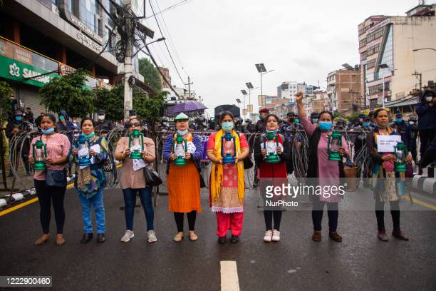 Protestors hold a lantern in a protest against killing of Dalit low-caste youth in Rukum district during lockdown in Kathmandu, Nepal on Thursday,...