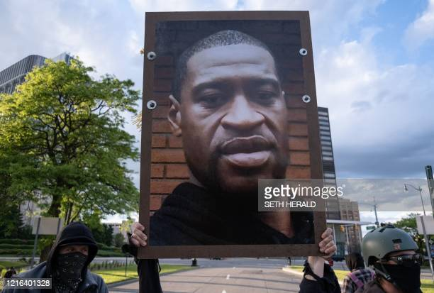 Protestors hold a picture of George Floyd at a protest in Detroit Michigan on May 30 2020 to protest the killing of George Floyd who died while a...