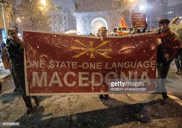 Protestors hold a placard as they take part in a protest march with others as snow falls in Skopje on February 27 2018 Rightwing and diaspora...