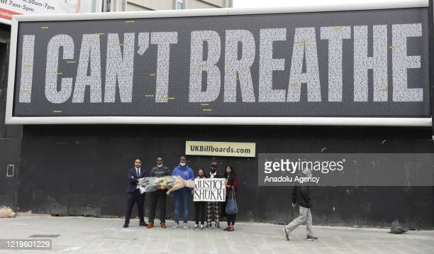 "Protestors hold a placard asking for justice for Shukri Abdi in front of a billboard with a slogan reading ""I can't breath"" in support of the Black..."