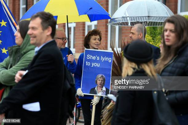 Protestors hold anti-Conservative and pro-Labour placards as they wait for the arrival of Britain's Prime Minister Theresa May for a campaign meeting...