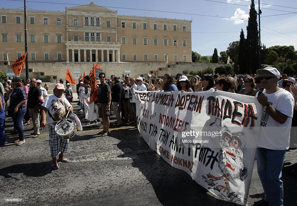 Protestors hold banners during a demonstration against austerity and job cuts on September 18, 2013 in Athens, Greece. As part of the redeployment plan in the country reeling from six years of recession, civil servants have to accept new posts or spend eight months on reduced salaries as alternative posts are found, with the risk of losing their jobs altogether.
