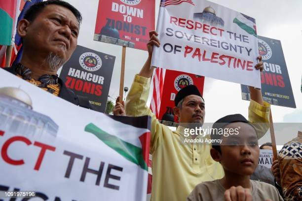 Protestors hold banners outside the Putra mosque during a demonstration against Israeli citizen entering Malaysia in Putrajaya Malaysia on February 1...