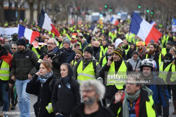 Protestors hold French flags during an antigovernment demonstration called by the Yellow Vests Gilets Jaunes movement near the Eiffel tower in Paris...