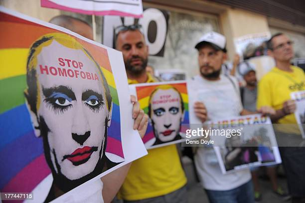 Protestors hold graphic images of Russian President Vladimir Putin wearing lipstick during a protest against Russian antigay laws opposite the...