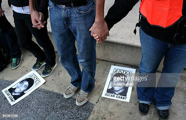 Protestors hold hands as they pray during a demonstration for slain 22yearold Oscar Grant III January 14 2009 in Oakland California Twelve days after...