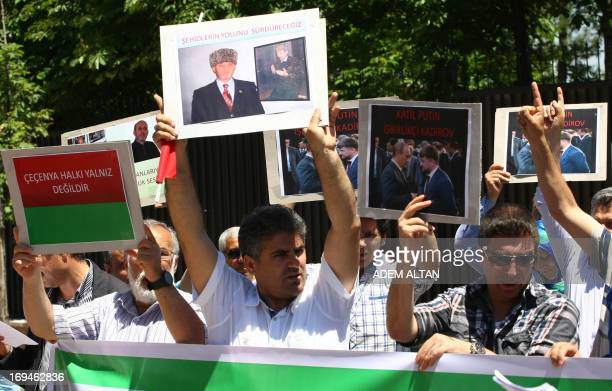Protestors hold images of Medet Unlu a Chechen activist based in Turkey who was killed on May 22 as they protest his death outside the Russian...