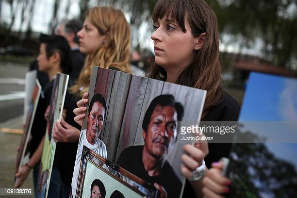 Protestors hold photos of Ecuadorian people who were affected by pollution from dumped toxic waste during a demonstration outside of the Chevron...