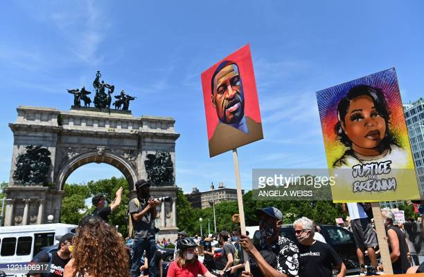 Protestors hold pictures of George Floyd and Breonna Taylor as they march during a Juneteenth rally at Grand Army Plaza on June 19, 2020 in the...