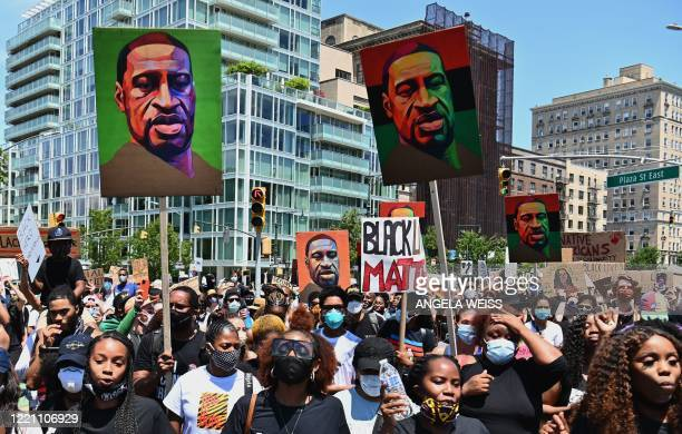Protestors hold pictures of George Floyd as they march during a Juneteenth rally at Grand Army Plaza on June 19, 2020 in the Brooklyn Borough of New...