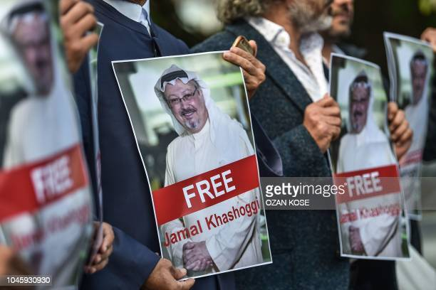 TOPSHOT Protestors hold pictures of missing journalist Jamal Khashoggi during a demonstration in front of the Saudi Arabian consulate in Istanbul on...