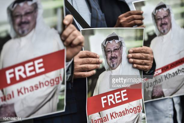 TOPSHOT Protestors hold pictures of missing journalist Jamal Khashoggi during a demonstration in front of the Saudi Arabian consulate on October 8...