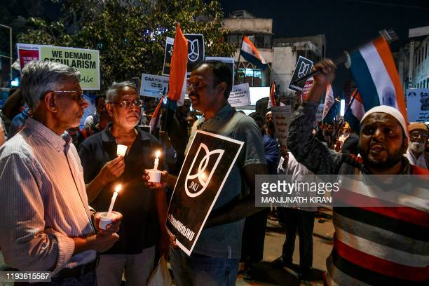 Protestors hold placards and national flags as they stage a candle light vigil condemning Indian Prime Minister Narendra Modi and India's new...