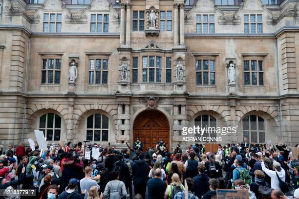 Protestors hold placards and shout slogans below a statue of British imperialst Cecil John Rhodes during during a protest called by the Rhodes Must...