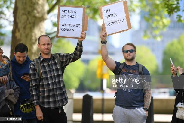 Protestors hold placards as a small group of anti-lockdown protesters gather outside New Scotland Yard in Victoria, London on May 2 during the...