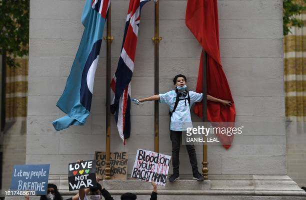 TOPSHOT Protestors hold placards as they demonstrate by the Cenotaph war memorial on Whitehall during an antiracism demonstration in London on June 3...