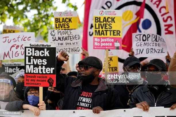 Protestors hold placards during a demonstration on the one year anniversary of the Death of George Floyd, in Windrush Square, Brixton in south London...