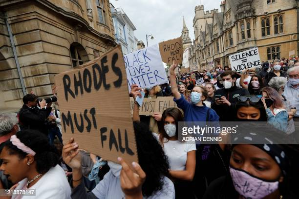 Protestors hold placards during a protest called by the Rhodes Must Fall campaign calling for the removal of the statue of British imperialist Cecil...