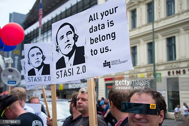 Protestors hold posters reading 'Stasi 20' depicting US President Barack Obama wearing headphones in allusion of a film poster of the movie 'The...