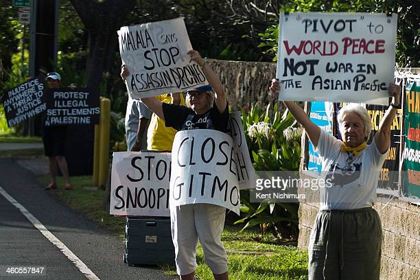 Protestors hold signs as US President Barack Obama's motorcade returns to his vacation compound at Kailuana Place upon returning from a hiking the Na...
