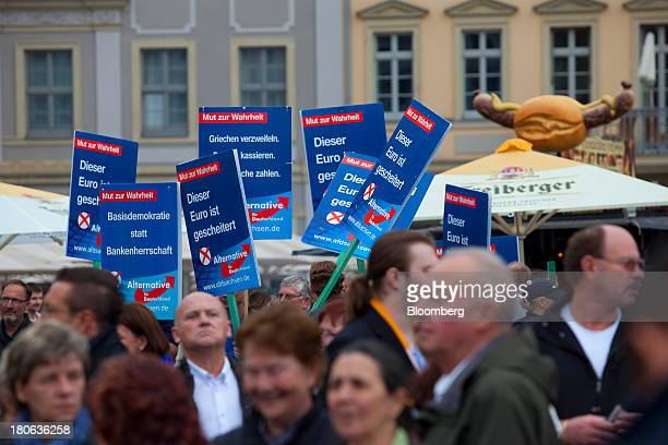 Protestors hold signs before Angela Merkel Germany's chancellor and party leader of the Christian Democratic Union speaks at an election rally in...
