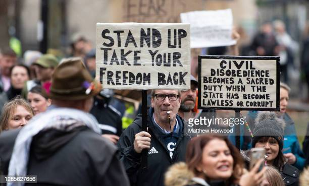 Protestors hold signs on November 14, 2020 in Bristol, England. Police had warned protesters to cancel the march or face possible fines. Throughout...