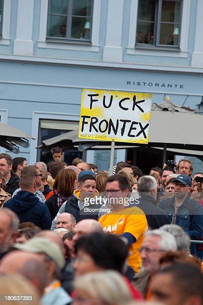 Protestors hold signs while Angela Merkel Germany's chancellor and party leader of the Christian Democratic Union speaks during an election rally in...