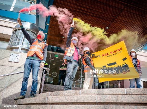 Protestors hold smoke flares as they take part in an action called by global environmental movement Extinction Rebellion and Dutch climate activist...