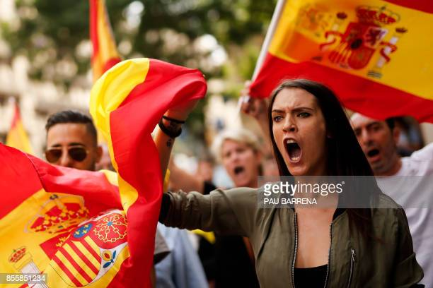Protestors hold Spanish flags during a demonstration against independence in Catalonia called by the xenophobic farright party 'Platform for...
