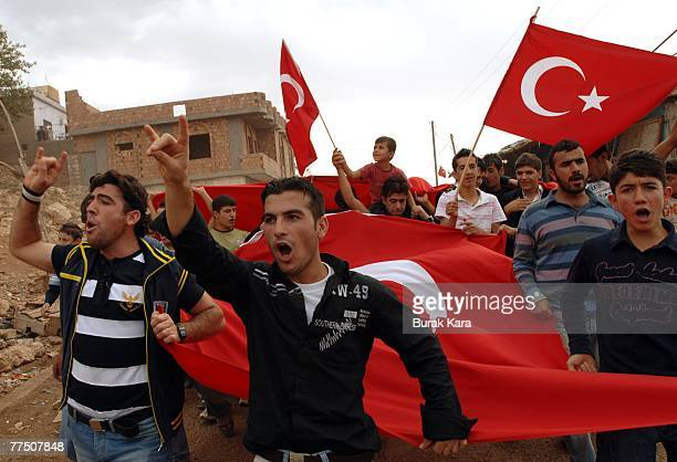 Protestors hold Turkish flags aloft and shout slogans against the outlawed Kurdistan Workers Party as they march through the village of Gorumlu on...