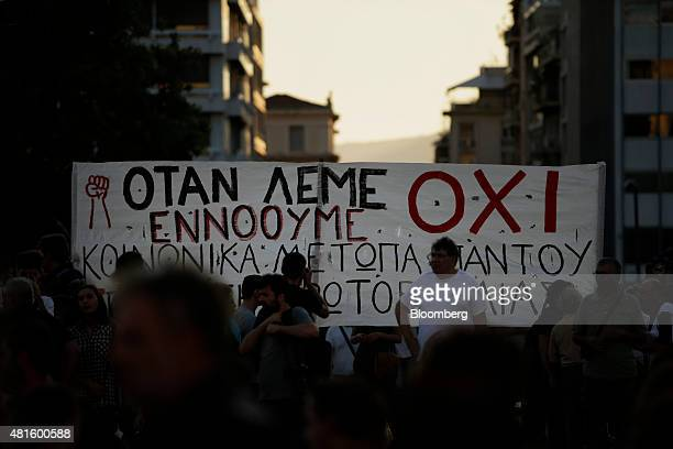 Protestors hold up a banner during an antiausterity demonstration at Syntagma Square in Athens Greece on Wednesday July 22 2015 Finance Minister...