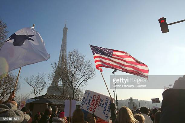 Protestors hold up a US Flag and anti Trump signs as over 2000 people protest during the Women's march on the Trocadero in front of the Eiffel Tower...