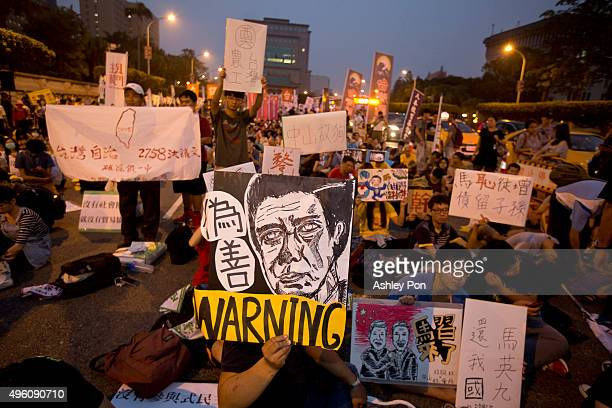 Protestors hold up caricatures during a demonstration against the meeting between Taiwan's President Ma Ying-jeou and Chinese President Xi Jinping in...