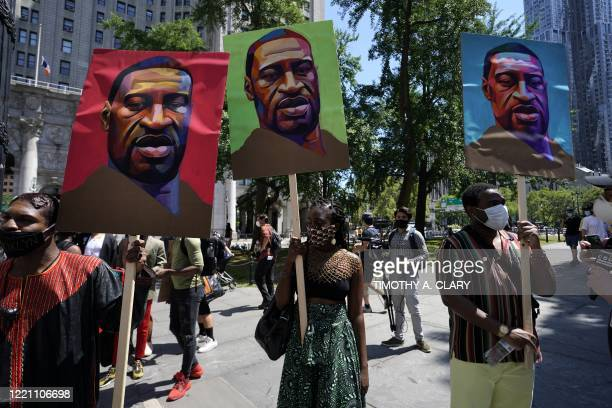 Protestors hold up pictures of George Floyd at Foley Square during a Juneteenth rally in New York on June 19, 2020. - The US marks the end of slavery...