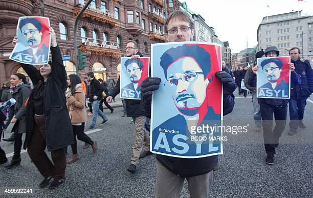 Protestors hold up placards featuring a picture of former NSA contractor Edward Snowden and with the world Asylum on it during a march against the...