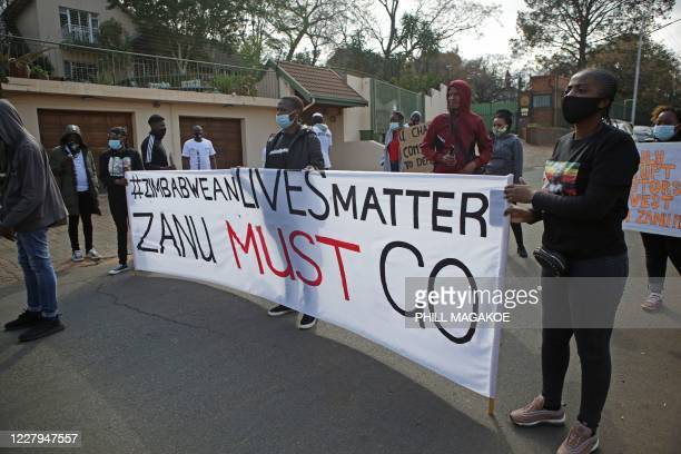 Protestors hold up plackards against the government of Zimbabwe's alleged state corruption, media freedom and the deteriorating economy outside the...