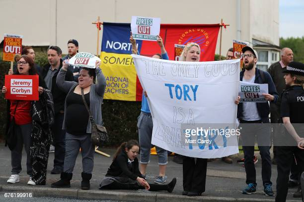 Protestors hold up signs as Britain's Prime Minister Theresa May makes a campaign stop on May 2 2017 in Bristol England The Prime Minister is...