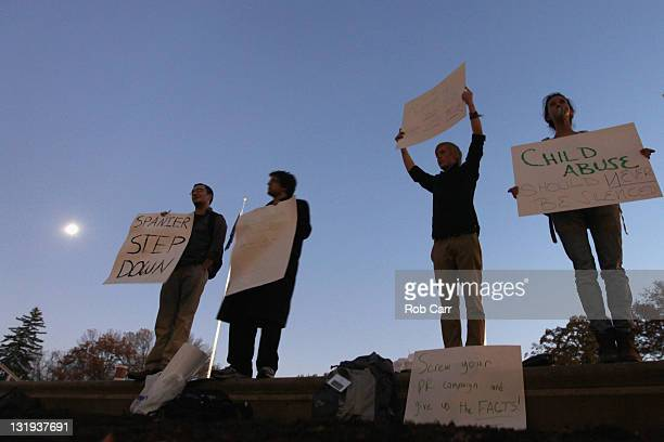 Protestors hold up signs outside the Administration building on the campus of Penn State University calling for the resignatation of the school's...