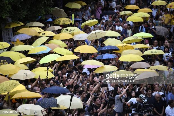 Protestors hold up yellow umbrellas during a gathering outside the government headquarters to mark the third anniversary of mass prodemocracy rallies...