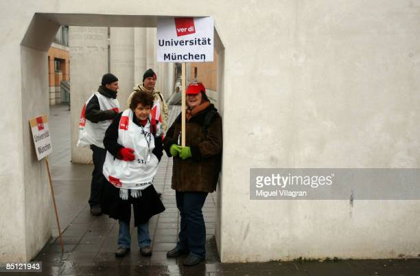 Protestors holding a poster reading 'University Munich' search protection from the rain during a protest rally on February 26 2009 in Nuremberg...