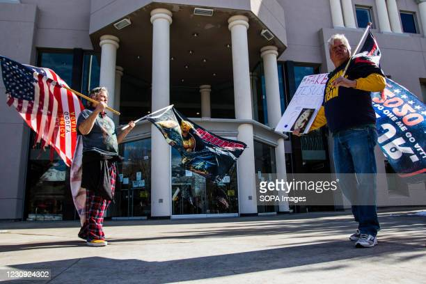 Protestors holding flags stand in front of the states legislative building during the demonstration. Protesters gathered at the state's legislative...