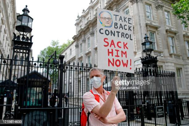 Protestors holding placards calling for there resignation or sacking of Number 10 special advisor Dominic Cummings demonstrate outside the entrance...